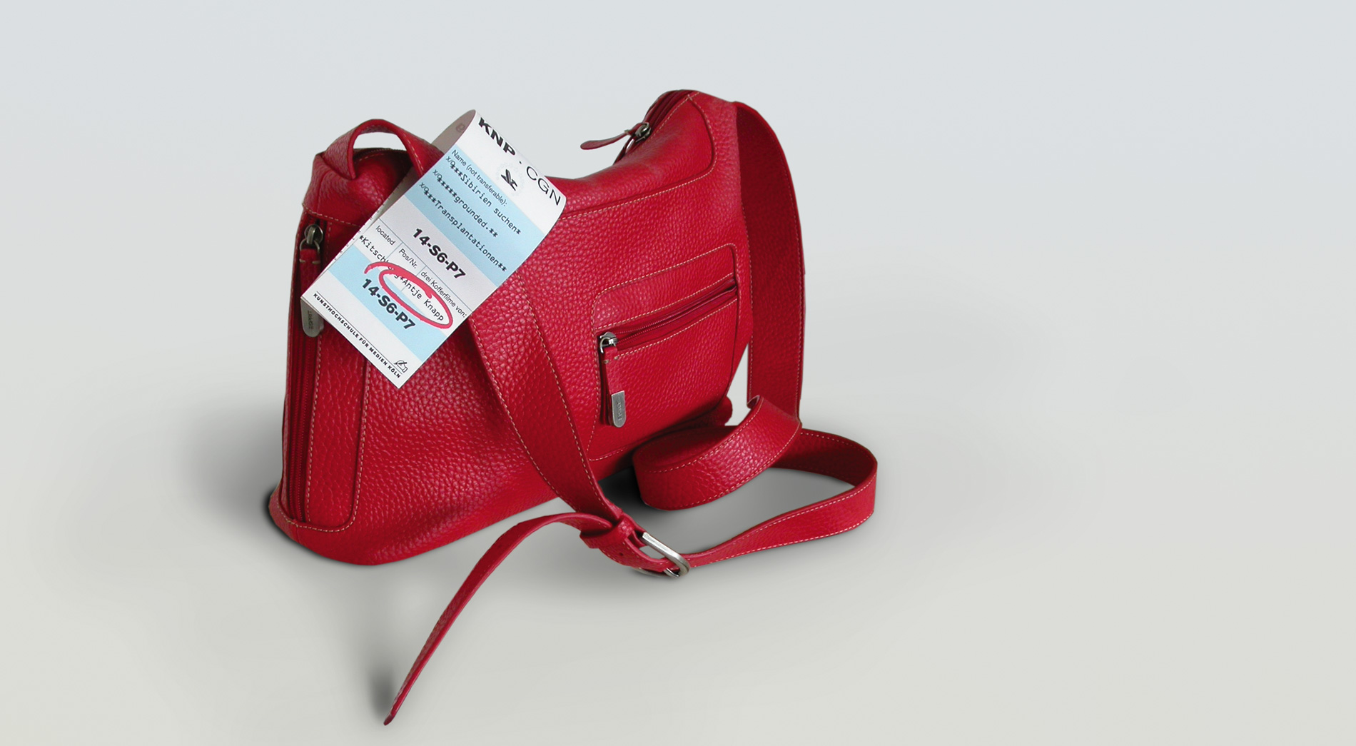 Flyer/Baggage Tag zur Filpremiere am Taschengurt befestigt